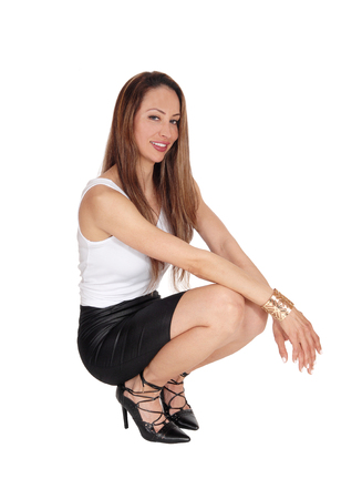 A beautiful young Caucasian woman in a white top and black leather skirt crouching in the floor and smiling, isolated for white background