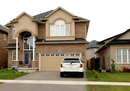 A new big house in a subdivision in Hamilton, Canada with a white carsitting on the driveway