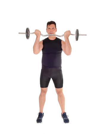 A middle age tall man standing from the front and lifting the weight in a black exercising outfit, isolated for white background