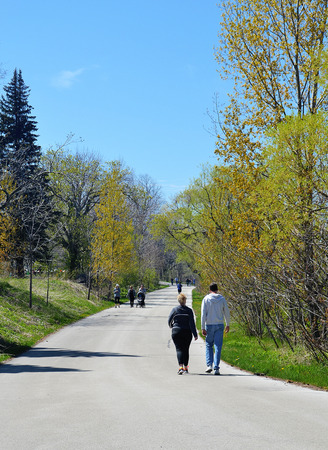 People are walking on a walkway in the park on a sunny spring dayunder blue sky