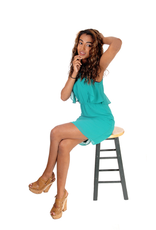 A beautiful slim woman in a short dress sitting isolated on hair with her
