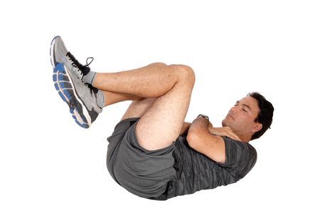 A young tall man lying on the floor doing his exercise in sit-ups in shorts and sneakers, isolated for white background Stock Photo