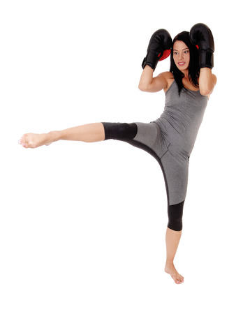 A slim young woman in exercising outfit praxis kick boxing with herblack cloves, standing on one leg, isolated for white background Standard-Bild - 108919697