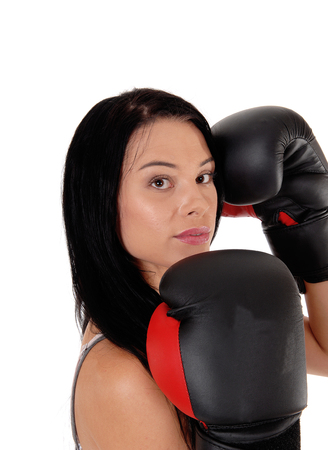 A young woman looking into the camera with her black boxing cloves and black hair, ready for the fight, isolated for white background Stock Photo