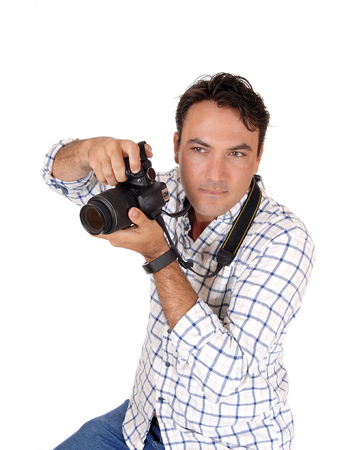 A close-up image of a handsome man holding his camera ready of a  shoot, looking sharp, isolated for white background