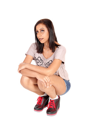 A lovely young woman with black hair crouching on the floor in