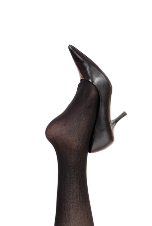 A closeup image of a woman leg in black pantyhose lifted up with a