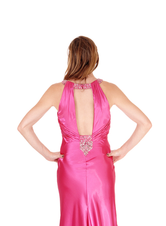 A slim lovely young woman standing in a long pink evening gown from