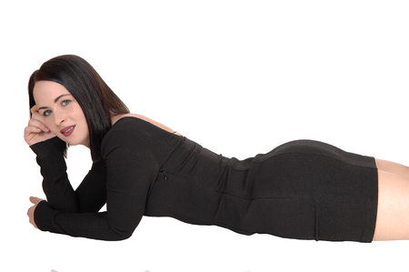 Una hermosa joven acostada con un vestido negro y cabello negro sobre su estómago en el suelo con su bonita figura, aislado de fondo blanco.