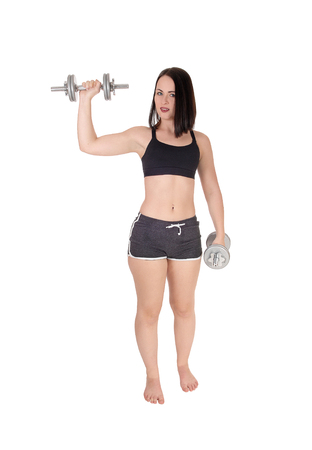 A beautiful young woman standing bare feet in her sports outfit working out with two dumbbells, isolated for white background