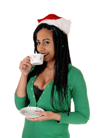 A young smiling woman drinking her morning coffee in her green nighty