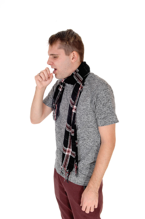 Ayoung man standing in a sweater and a scarf around his neck holding hand on his mouth and coughing, isolated for white background Stock Photo