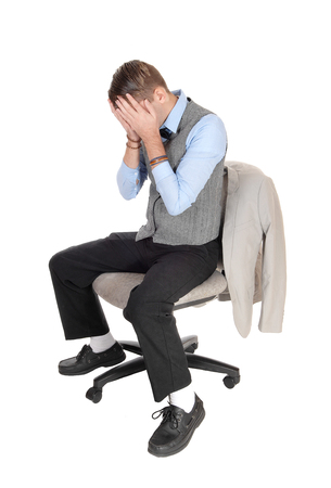A depressed man in a gray vest sitting on a chair with both hands over 