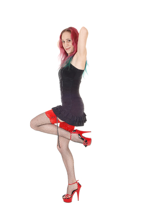 A gorgeous young woman standing in profile in a short black dress and stockings with her red hair hands on head isolated for white background