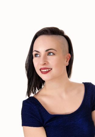 Eine schöne junge Frau in einer Nahaufnahme mit kurzen schwarzen Haaren, die auf einer Seite rasiert sind, nach oben schauend, isoliert auf weißem Hintergrund