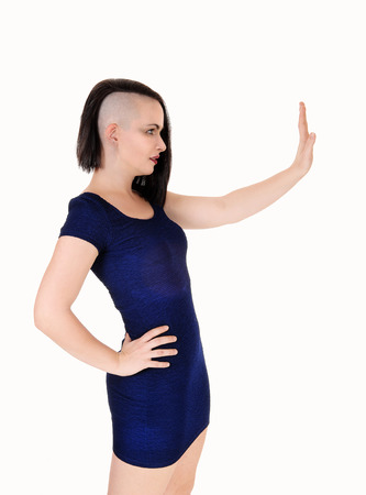 A gorgeous young woman in a tight blue dress standing in profile with
