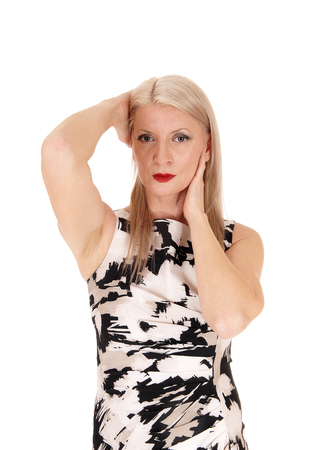 A beautiful middle age woman in a summer dress standing from frontwith both hands on her head, isolated for white background