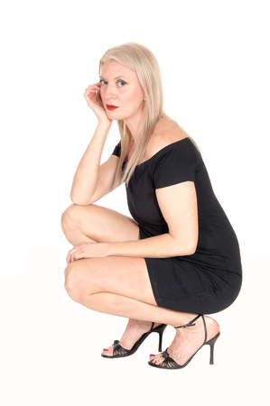 A beautiful blond woman in a short black dress crouching on the floorin high heels, hand on her face, isolated for white background Stock Photo