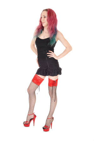A gorgeous young woman standing from front in a short black dress  and stockings with her red hair, isolated for white background