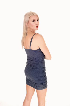 A beautiful blond woman standing from the side in a short blue dresswith her slim figure, isolated for white background
