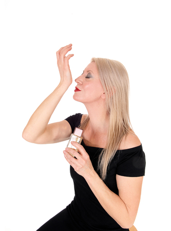 A gorgeous blond woman sitting in a black dress and smelling her new