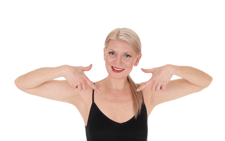 A close up image of a smiling blond woman in a black top pointing