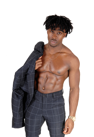 A young alethic black man standing shirtless with his suit jacket over his shoulder, showing his great body, isolated for white background