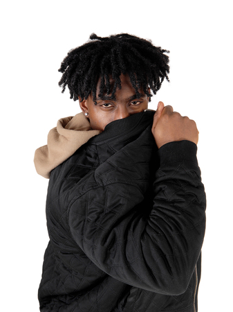 An African American man standing in the studio hiding his face behind his jacket looking at the camera, isolated for white background