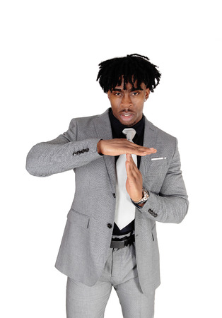 A handsome African American man standing in a gray suit and tiesigning with his hands he likes to talk, isolated for white background Stok Fotoğraf