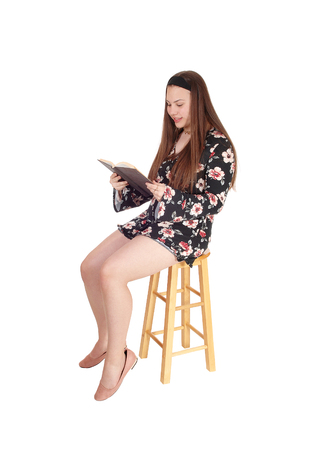 A full body image of a young teenage girl sitting in shorts on a chairreading in a book, isolated for white background