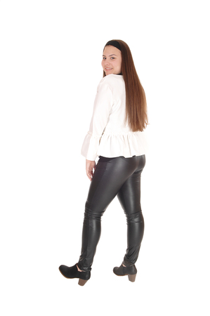 A teenager girl standing in black leather pants and a white jacket inprofile, looking over her shoulder, isolated for white background