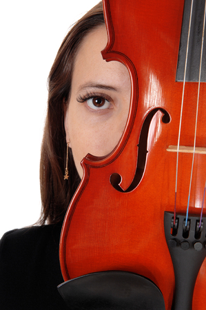 The eye of a beautiful woman hiding behind a violin looking into the