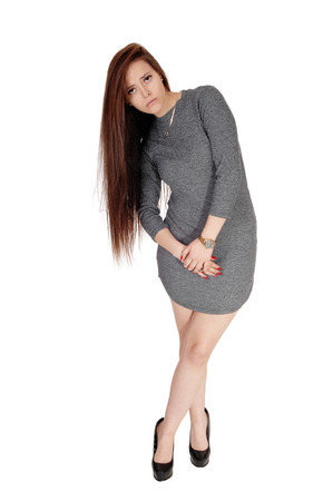 Pretty woman in gray dress bending side warts, her long brunette hair