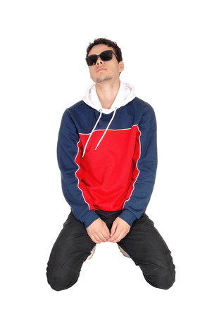 A handsome young man wearing sunglasses kneeling on the floorin sports clothing, taking a rest, isolated for white background
