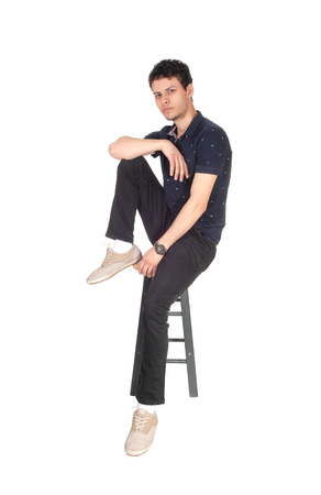 A good looking young man in black clothing sitting on a chair in thestudio, resting, isolated for white background