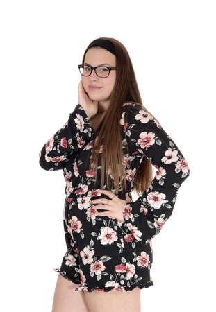A beautiful young teen girl standing in shorts and glasses isolated forwhite background with one hands on her face
