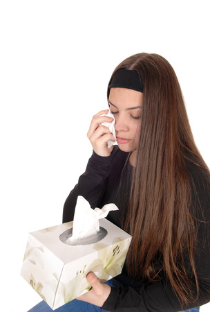 A beautiful young teen girl crying with a tissue in her hand wiping the tears of, and holding the Kleenex box, isolated for white background
