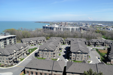 An aria view of some big development with new houses and condobuildings on the shore of lake Ontario on a sunny spring day Stok Fotoğraf - 124387390