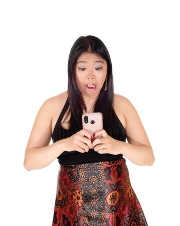A young Chinese woman standing in a dress holding her cell phoneand is shocked about the message she got, isolated for white back