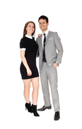 A happy young couple in suit and dress standing smiling isolated for