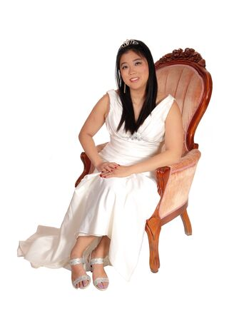 A beautiful young Chinese bride sitting in a old fashion armchair in a 
