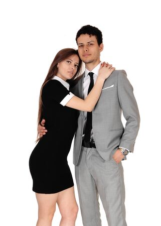 A beautiful young couple standing in a gray suit and black dress in a 