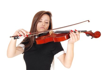 A beautiful woman standing in a black dress playing her violin with her eyes closed, isolated for white background Stock Photo
