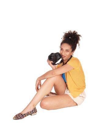 Eine junge Frau aus verschiedenen Rassen, die mit ihrer Kamera auf dem Boden sitzt, mit ihrem lockigen schwarzen Haar, das den Fotografen ansieht, isoliert für weißen Hintergrund
