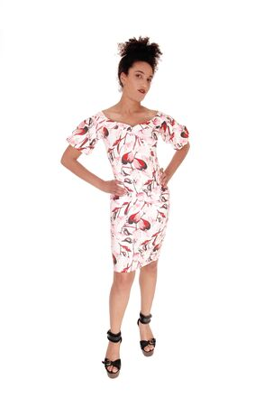 Multi-racial woman standing from the front in a summerdress holding with her hands on her hip and a slim figure and curly blackhair, isolated for white background