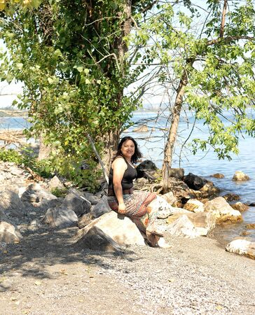 A lovely young woman sitting on the lake Ontario on a bright summer day on some rocks 版權商用圖片
