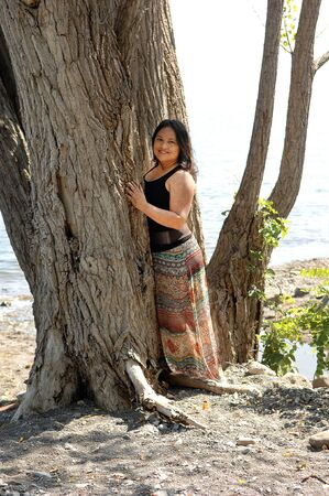 A beautiful young woman standing in the park on a big tree on the shore of lake Ontario in a bright sunny day 版權商用圖片