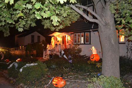 Ein Nachtbild eines schön dekorierten Hauses mit Halloween Dekoration unter einem großen Baum Standard-Bild