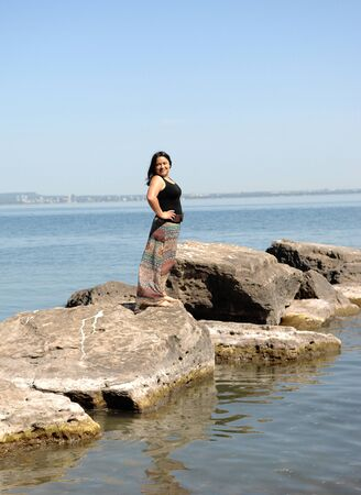 A happy Hispanic young woman standing on some rocks in the lake Ontario on a beautiful bright summer day