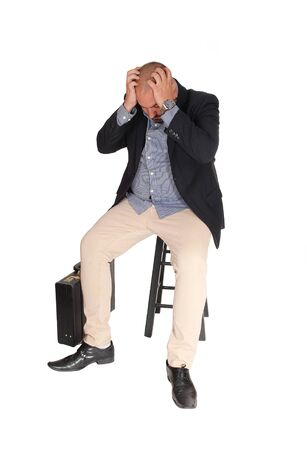 A middle age business man sitting with his hands on his head thinking about his problem, isolated for white background